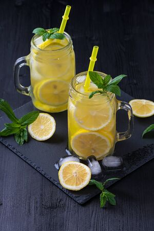 Lemonade in a jar with ice and mint on a black wooden table..