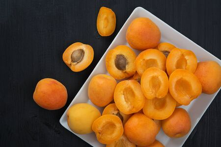 Fresh apricots in a plate on a wooden black table. 写真素材