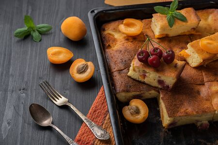 Fruit tart and apricots on a black wooden table.
