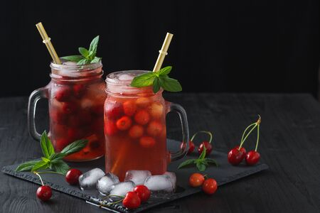 Fresh summer cocktail with sweet cherry and ice cubes on a dark background on a black wooden table. 写真素材