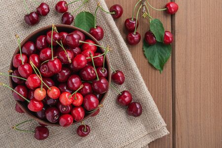 Fresh sweet cherry on a plate on a wooden table. 写真素材