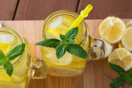 Lemonade in a jar with ice and mint on a black wooden table 写真素材
