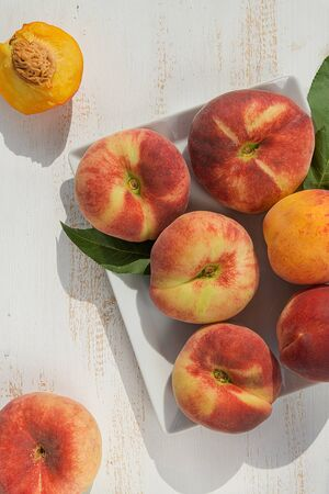 Fresh ripe peaches in a plate on a white wooden background. Fresh fruit background. Summer fruits.