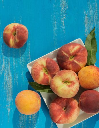 Fresh ripe peaches in a plate on a blue wooden background. Fresh fruit background. Summer fruits.