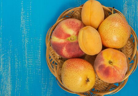 Fresh ripe peaches, pears and apricots in a plate on a blue wooden background. Fresh fruit background. Summer fruits. 写真素材