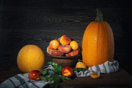 Still life with peaches, pumpkin, fruits and melons on a wooden table.