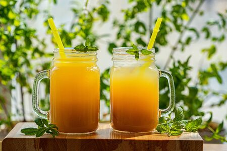 Peach cocktail or tea with ice and mint on a green background