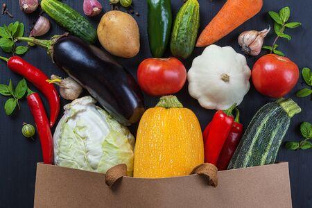 Bag of fresh vegetables on a black wooden table.