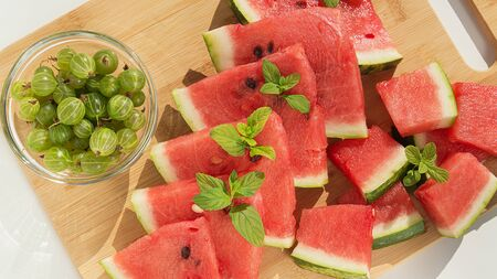 Fresh slices of watermelon and gooseberries on a wooden board. 写真素材