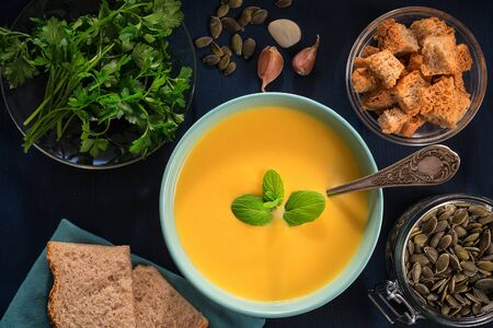 Pumpkin soup, pumpkin seeds, parsley and bread on a blue wooden table