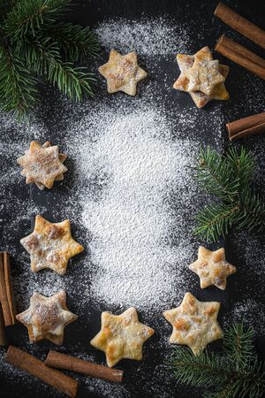 Christmas background with homemade cookies, cinnamon and spruce