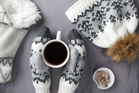 Warm knitwear: mittens, hat, scarf and cup of coffee on a gray rustic wood background. Winter cozy still life. Top view