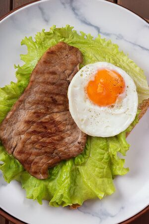 Fried egg and steak on bread for breakfast on plate and rustic table