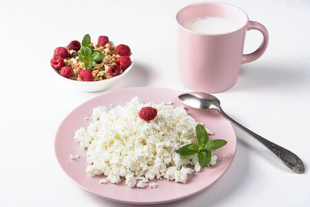 Cottage cheese in a pink plate, muesli and milk isolated on a white background Stock fotó