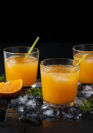 Tangerine cocktails with sliced mandarins, ice, mint on a black wooden table Stock fotó