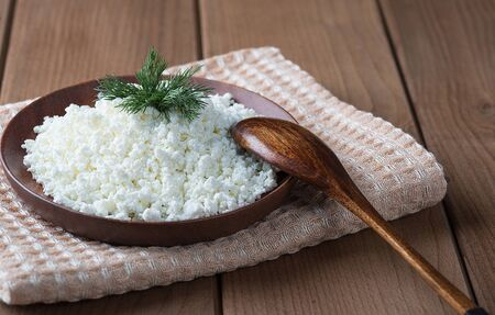 Cottage cheese in a wooden plate on a wooden table Stock fotó