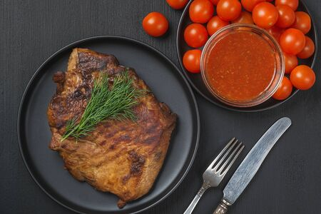 Grilled pork steak, tomatoes and sauce in a plate on a black table. View from above.