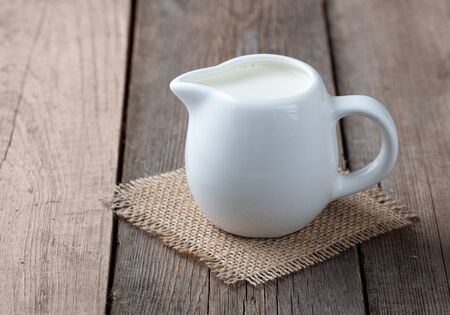 White jug with milk on a wooden rustic background