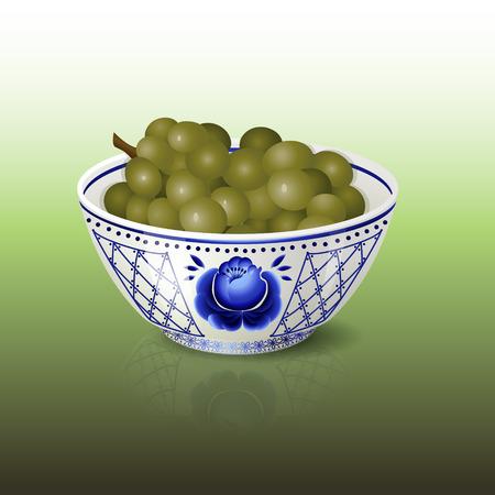 ensalada de frutas: bol con el ornamento floral azul y uvas en un fondo verde