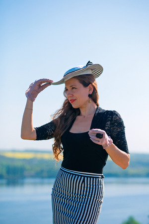 Retro styled girl with a hat in the open air