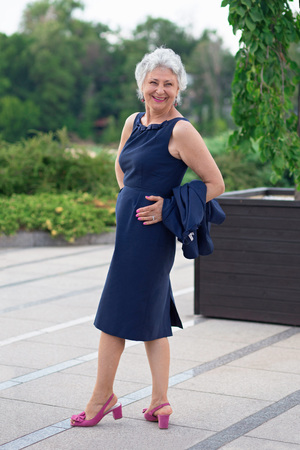 Senior woman in blue dress posing and smiling