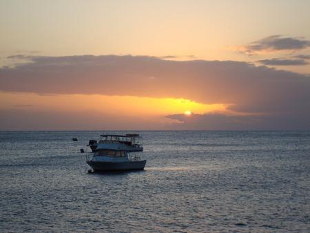 日没、ドミニカ国、カリブ海での水のボート 写真素材