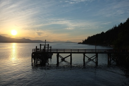 日没、ヴェスヴィオ山、ソルト スプリング島, BC, カナダのドックします。