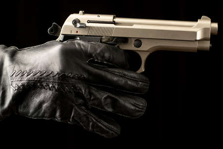 black background close-up black leather glove held dangerous knife and firearm consept visual design Stock Photo