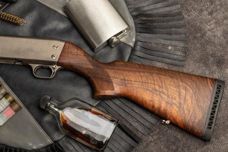 close-up on leather bag walnut wood stock pump shotgun cartridge steel flask glass coffee bottle concept