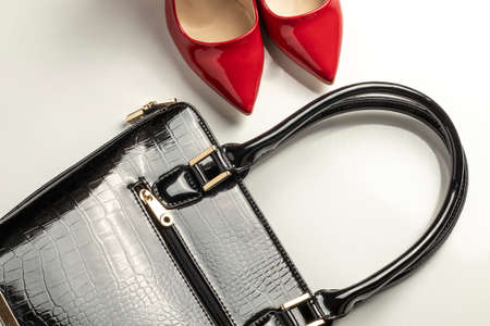 close-up of a white background black leather bag accessories and a pair of strappy red high-heeled women's shoes Stock fotó