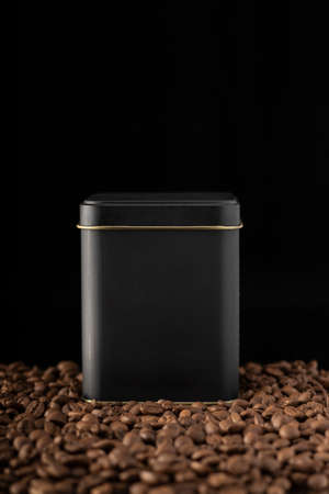 close-up black background black tin can inside and outside with coffee grains, next to old porcelain cup