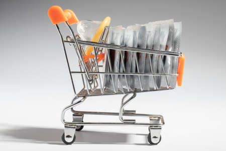 Packaged and open condoms in close-up concept supermarket trolley