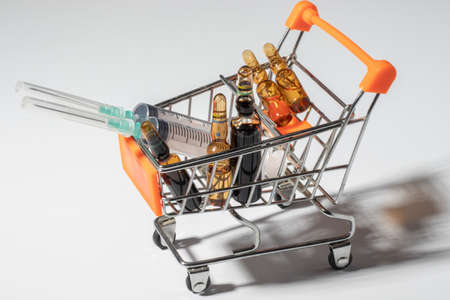 ampoule needles, colorful mixed medicine pills and medical syringe in close-up concept supermarket trolley