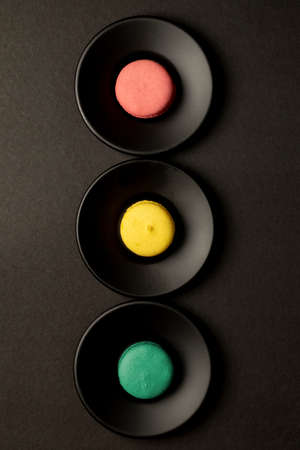 traffic light concept design of colored macarons on black background in close-up