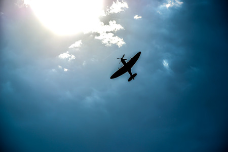 Spitfire silhouette in flight on blue sky abstract