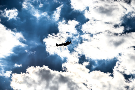 Spitfire silhouette on dark blue sky and snow white clouds