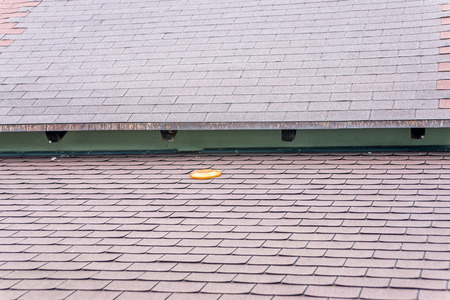 slate roof: Orange frisbee forgotten on brown asphalt roof