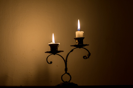 somber: Two small candles on holder over melted wax, in dark