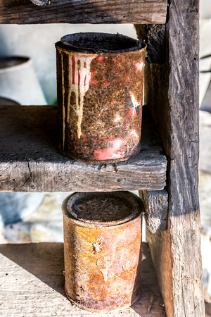 metallic stairs: Old rusty cans, forgotten on old wooden stairs