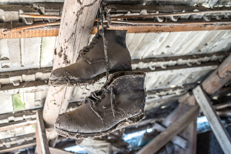 attic: Old leather pair of working shoes hanging from attic