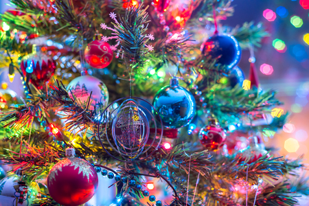 Part of Christmas tree, with colorful glass balls, small decorations and colorful light reflections Stock Photo