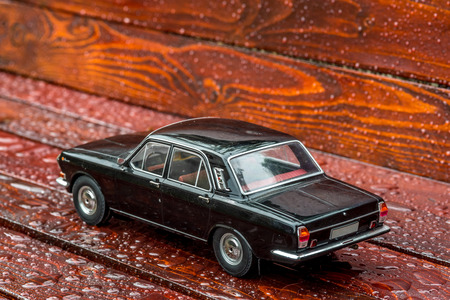 Black model car limousine on mahagony boards
