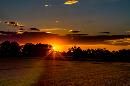Harvested grain field on countryside at sunset Stock Photo