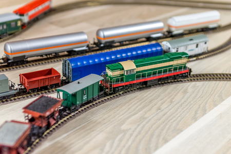 Green model diesel engine pull freight train on light wooden floor, playtime for kids and adults Stock Photo