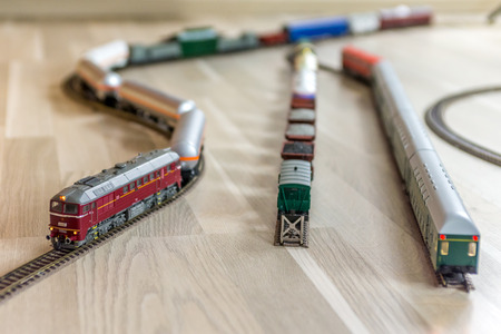 Bordeaux model soviet diesel engine pull heavy freight train on light wooden floor, playtime for kids and adults Stock Photo