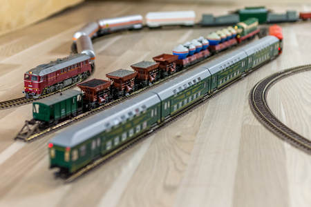 Model train depot with many train cars on wooden floor, game for kids and adults Stock Photo
