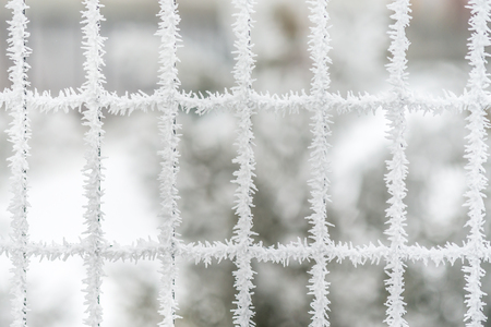 Many fence windows with frozen snow crystals on surface Stock Photo
