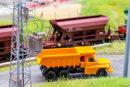 Orange truck on model train layout with moving freight train in behind