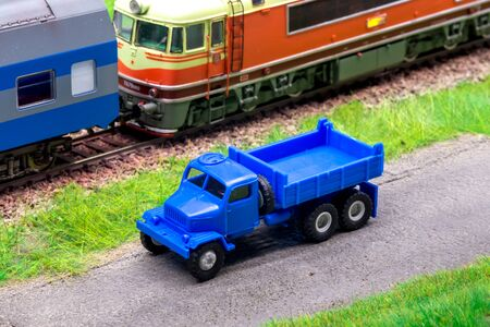 Blue scale truck on model train railroad layout road near train Stock Photo - 149338211