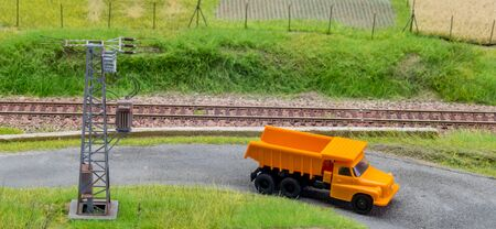 Orange truck in H0 scale on model train road Stock Photo - 149337397